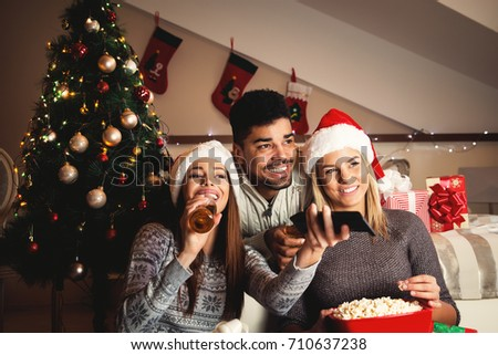 Beautiful happy young friends are watching tv for Christmas eve with popcorn and drinks. #710637238