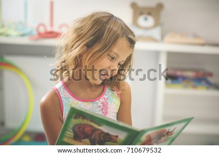 Little girl in playground. Little girl reading picture book.