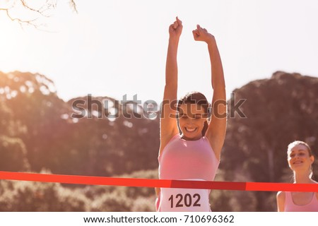 Happy female athlete with arms raised crossing finish line on sunny dy #710696362