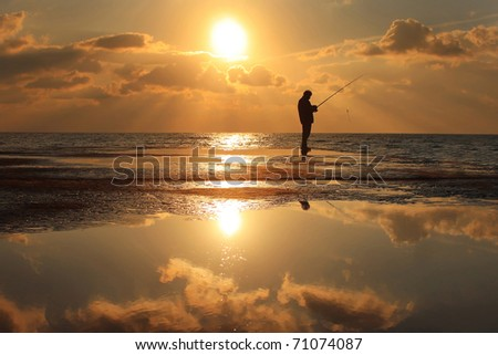 Fisherman standing on a pier at dawn sky background with sun rays and reflected in the sea water #71074087