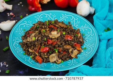 Delicious lentils with pepper and mushrooms on dark background #710787937