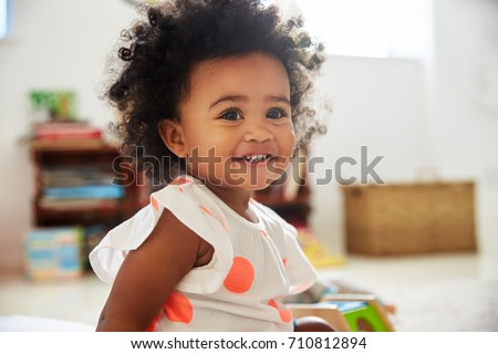 Happy Baby Girl Playing With Toys In Playroom Royalty-Free Stock Photo #710812894