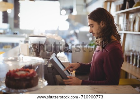 Side view of young waiter using cash register at counter in coffee shop #710900773