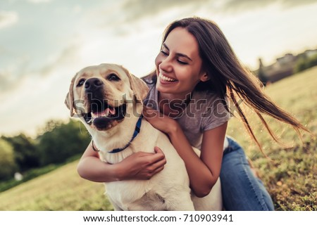 Attractive young woman with labrador outdoors. Woman on a green grass with dog labrador retriever. #710903941