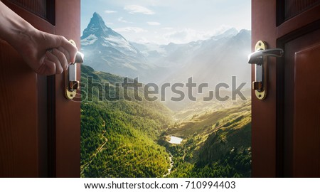 hand opens empty room door to nature and mountains Royalty-Free Stock Photo #710994403