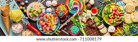 An assortment of colourful, festive sweets, ice-cream and candy in a panoramic orientation.
