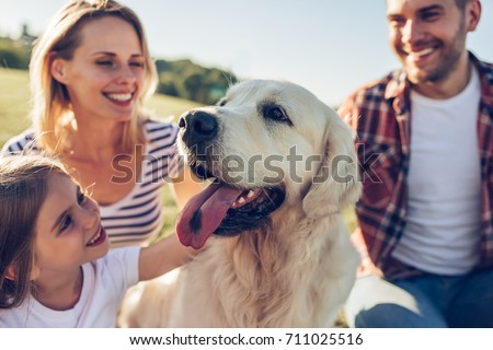 Beautiful happy family is having fun with golden retriever outdoors. Mother, father and daughter are sitting with dog labrador on green grass in park. #711025516