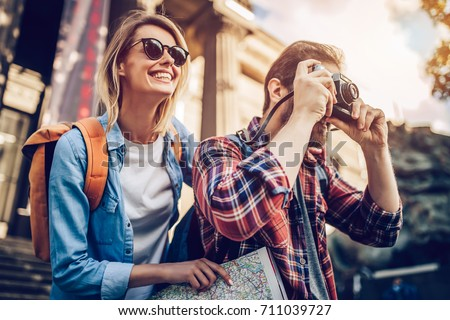 Couple of tourists is exploring new city together. Smiling and making photo on a retro camera. Royalty-Free Stock Photo #711039727