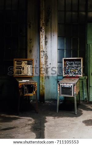 Two vintage but broken pinball machines were left behind at a break room inside an abandoned clothing factory. Royalty-Free Stock Photo #711105553