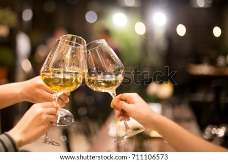 Shot in high iso with low light group of friend toasting with wine for celebration Royalty-Free Stock Photo #711106573