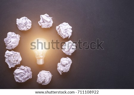Top view crumpled white paper and light bulbs on black stone board. Create idea concept #711108922