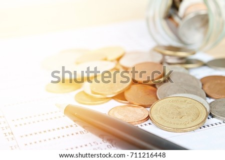 Business, finance, saving money, banking, loan, investment, taxes or accounting concept : Coins scattered from glass jar and pen on saving account book or financial statement #711216448