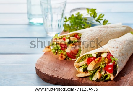Two fresh chicken and salad tortilla wraps on wooden cutting board with glasses in background Royalty-Free Stock Photo #711254935