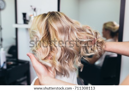 Beautiful hairstyle of young woman after dying hair and making highlights in hair salon. Royalty-Free Stock Photo #711308113