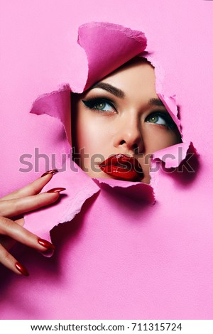 the face of a young beautiful girl with a bright make-up and with plump red lips peeks into a hole in pink paper.Fashion, beauty, manicure, make-up, color, sales, beauty salon, make-up artist.