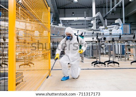 Exterminator in industrial plant spraying pesticide with sprayer. #711317173
