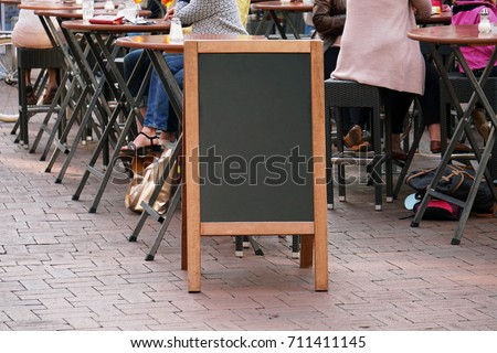 blank blackboard advertising sign or customer stopper at sidewalk cafe