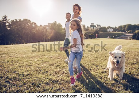 Beautiful happy family is having fun with golden retriever outdoors. Mother, father and daughter are running with dog labrador in park. #711413386