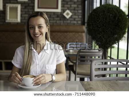 Beautiful young woman holding coffee in cafe #711448090
