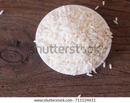 Uncooked sticky rice in white bowl on old wooden background. #711524611