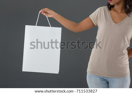 Mid section of woman holding shopping bag against gray background #711533827