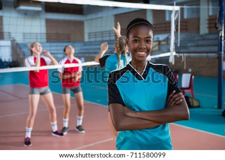 Portrait of smiling female volleyball player standing with arms crossed in the court #711580099