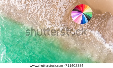 Colorful of umbrella on the beach and foam of blue sea wave from top eye view photo in outdoor sunlight lighting.