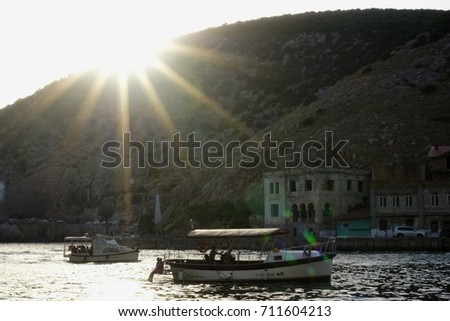 SEVASTOPOL - RUSSIA - JULY 2017. Yacht club Golden symbol with motor boats on water. Balaklava, Crimea. Bright white sun with long rays shines over mountain. Sunset yesterday, ruined houses background #711604213