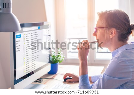 Female business person reading email on computer screen at work on internet #711609931