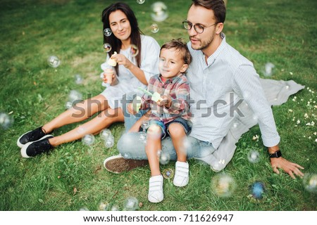 Happy young family playing with bubble wands with son in park outdoors in summer #711626947