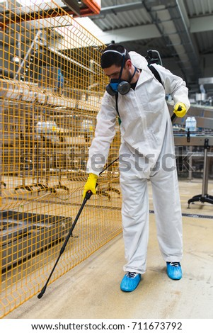 Pest Control Worker Hand Holding Sprayer For Spraying Pesticides in production or manufacturing factory #711673792