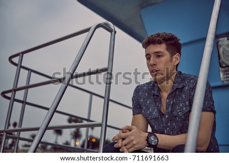 A man who is ready to cry on a lifeguard stand at dusk #711691663
