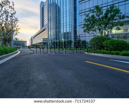 modern glass building with empty asphalt road at twilight,suzhou,china. #711724537