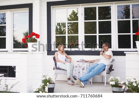 Happy young couple sitting and drinking tea on the porch #711760684