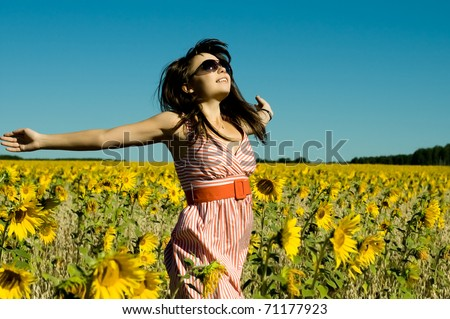 The young beautiful woman quickly runs on a glade of sunflower, smiles, hands are opened