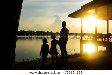 Lady and children stand by the lake in the evening #711814915