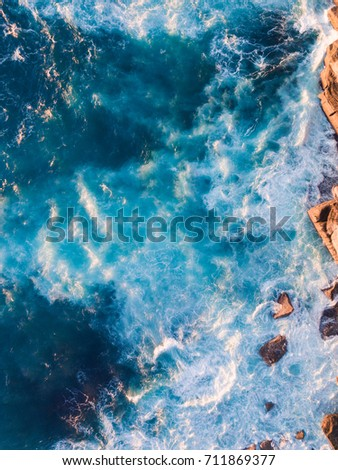 Aerial view of wave foam and rock cliff. #711869377