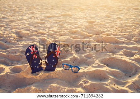 Thongs and sunglasses in sand on a beach, Australia day concept
