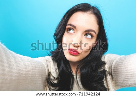 Young woman taking a selfie on a blue background #711942124