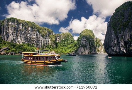 cruising among beautiful limestone rocks and secluded beaches in Ha Long bay, UNESCO world heritage site, Vietnam Royalty-Free Stock Photo #711950092