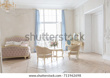 luxurious light interior in the Baroque style. A spacious room with a road chic beautiful furniture, a fireplace and flowers. plant stucco on the walls #711962698