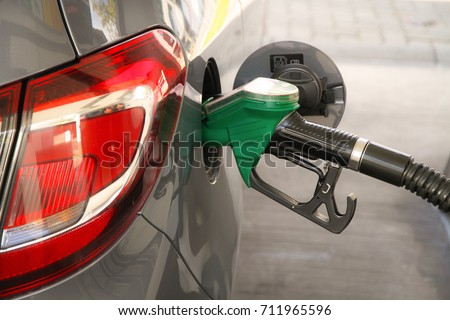 Car refueling at the petrol station. Concept for use of fossil fuels (gasoline, diesel) in combustion engines, air pollution and environmental and occupational health. #711965596
