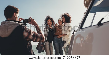 Young man photographing of female friends on seaside. Group of young people on road trip taking pictures.