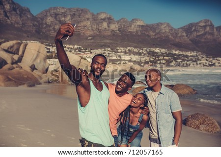 Group of friends taking selfie on beach. Best friends standing along rocky coastline and taking a self portrait with smart phone.
