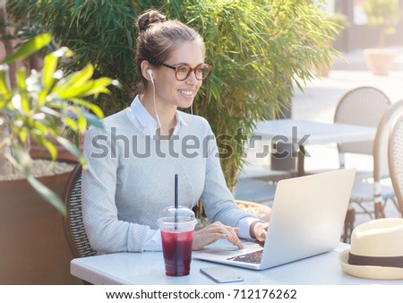 Closeup image of young European business woman wearing trendy eyeglasses, looking attentively to street while working on laptop with earphones on, dealing with current projects for work online #712176262