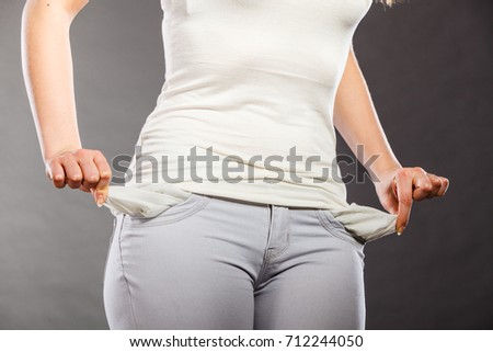 Financial difficulties, bad economy, no money concept. Young woman student girl showing empty pockets, part of body female hips wearing pants #712244050