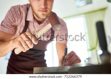 Closeup of unrecognizable craftsman working with metal and hammer in workshop #712266379
