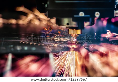 CNC Laser cutting of metal, modern industrial technology. Small depth of field. Warning - authentic shooting in challenging conditions. A little bit grain and maybe blurred. Royalty-Free Stock Photo #712297567