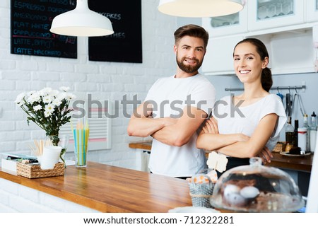 Two cheerful small business owners smiling and looking at camera while standing behind the counter in their restaurant #712322281