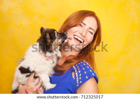 beautiful redhaired young woman standing with little cute dog puppy on yellow studio background #712325017